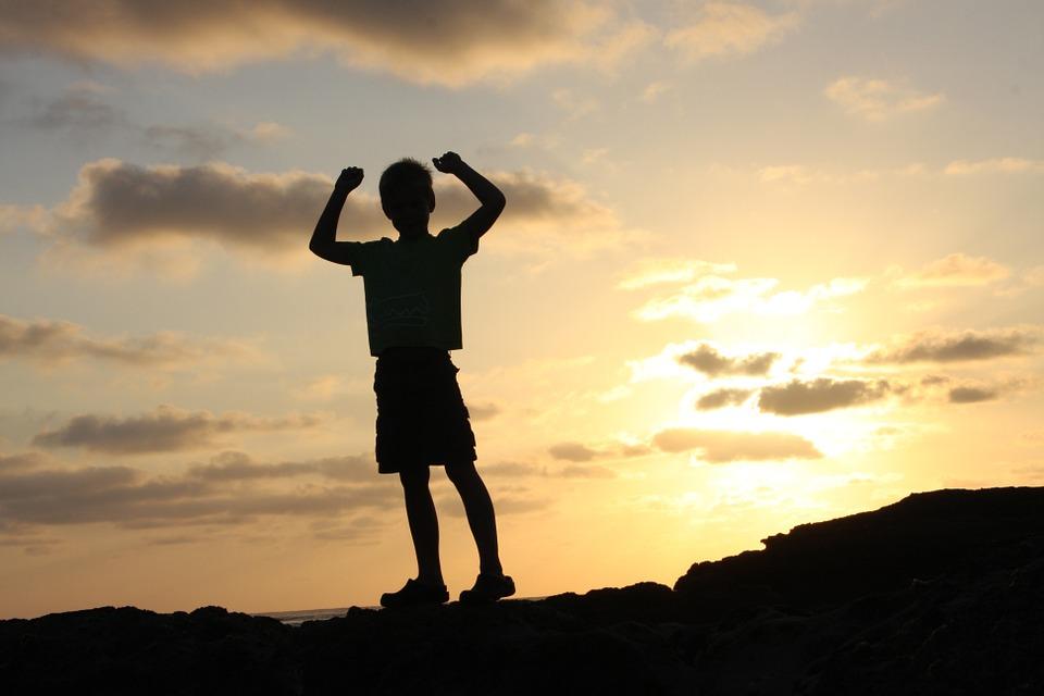 photo d'un garçon levant les bras